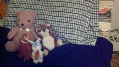 A bed with stuffed animals on a pillow.