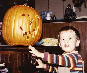 Toddler boy looking a bit wary of a carved pumpkin.